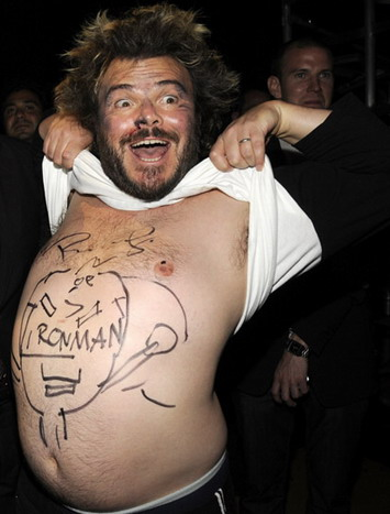 Jack Black lifting up his shirt to reveal writing on his chest.